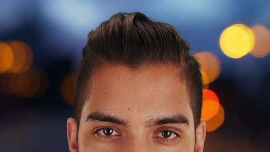 Close up of young Latin man with undercut outside at night with bokeh lights