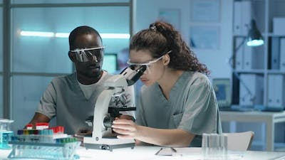 Multiethnic Scientists Working with Microscope in Lab