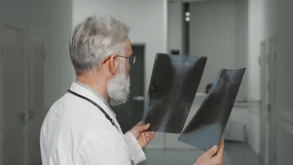Thumbnail for Senior Doctor Smiling To the Camera While Examining X-ray Scans