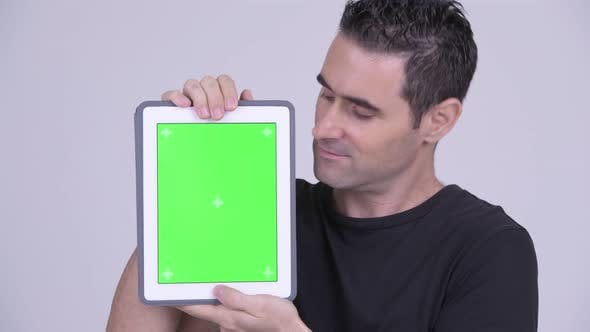 Thumbnail for Closeup of Happy Handsome Man Showing Digital Tablet Against White Background