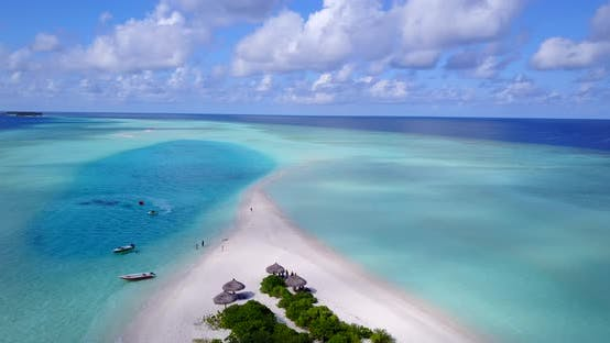Daytime overhead clean view of a sunshine white sandy paradise beach and blue water background in 4K