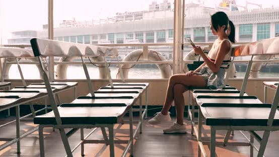 Thumbnail for Woman taking ferry in Hong Kong under sunset time