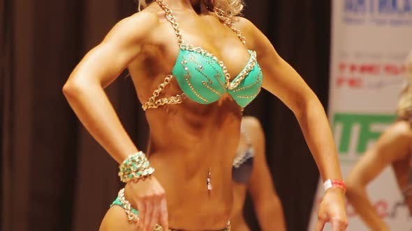 Tanned Female Demonstrating Relaxed Pose at Bodybuilding Contest, Ideal Body
