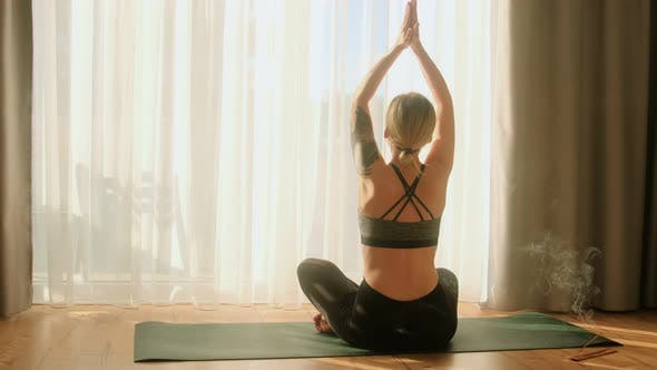 Woman doing morning yoga practice meditation namaste sun salutation at home