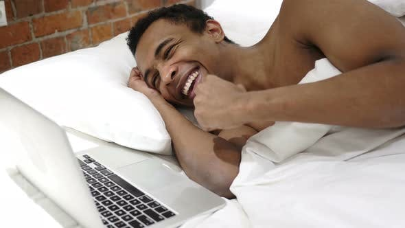 Thumbnail for African Man in Bed Working on Laptop and Reacting to Success