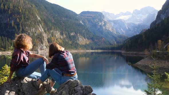 Thumbnail for Two Smiling Tourist Girls Sitting On A Shore Of Quiet Austrian Lake 2