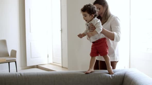 Cheerful Mother Helping Her Son to Walk on Sofa