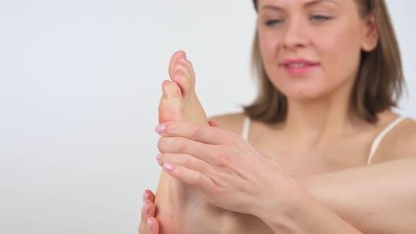 Woman Applying Cosmetic Foot Cream