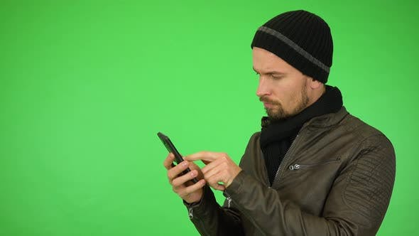 Cover Image for A Young Man in a Winter Outfit Works on a Smartphone, Then Smiles at the Camera - Green Screen