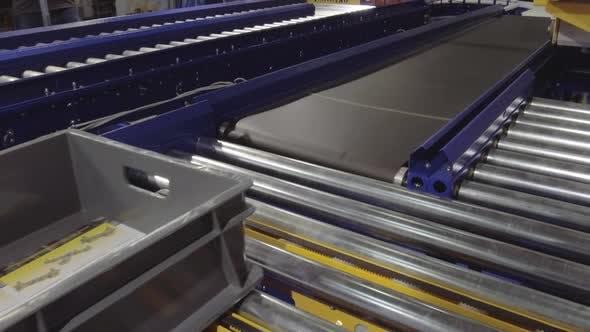 An Empty Plastic Box Moves Along a Roller Conveyor