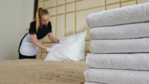 Hotel Concept. Young, Beautiful Maid in Uniform and Apron Making Bed in Room, Shot Through Stack of