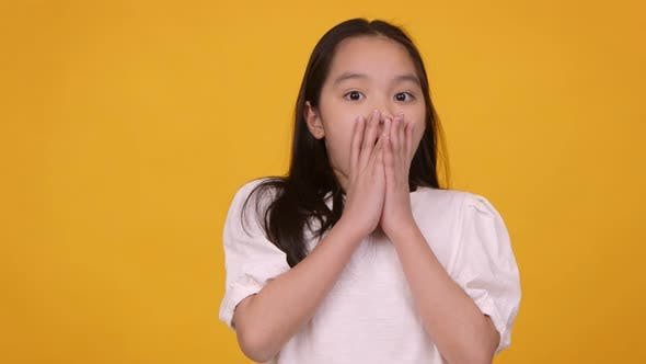 Shocked Little Asian Girl Feeling Surprised Closing Her Mouth in Amazement Orange Background