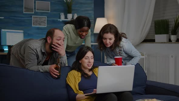 Multiethnic Friends Watching Interesting Comedy Movie on Laptop Computer