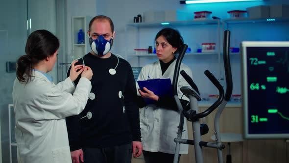 Scientist Researcher Preparing Man Patient for Endurance Test