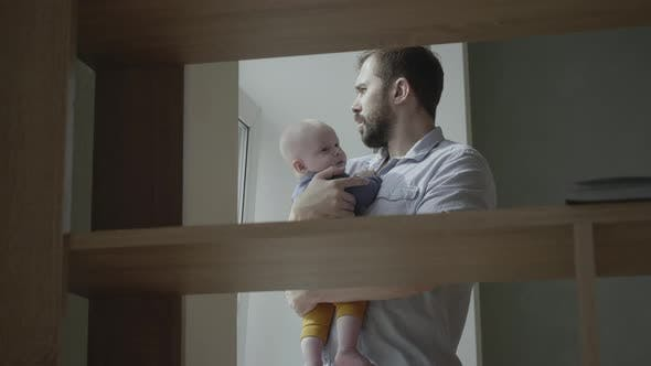 Thumbnail for Dad holding baby near a window.