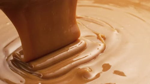 Pouring melted caramel, closeup food shot.