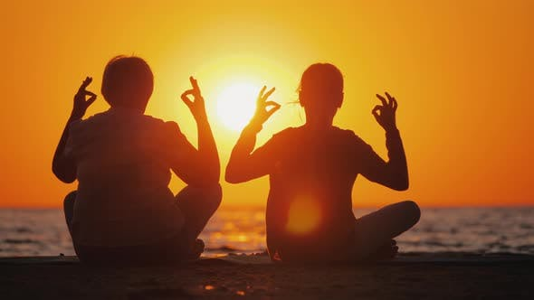 Thumbnail for Grandmother and Granddaughter Meditate on the Beach. Active and Healthy Seniors Concept