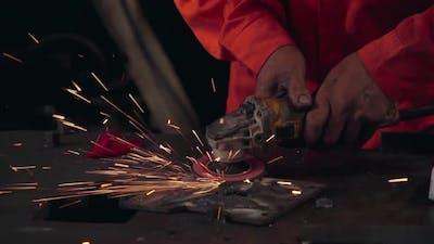 Professional mechanic is cutting steel metal.