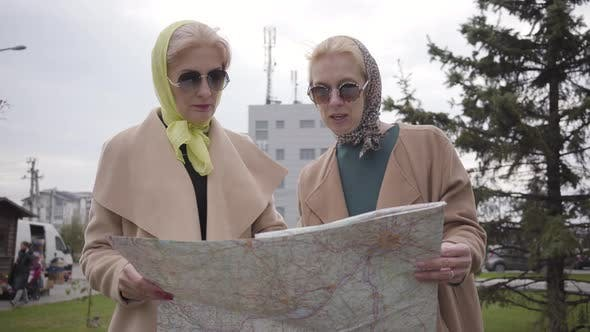 Thumbnail for Two Mature Women in Headscarves and Sunglasses Holding the Map and Talking
