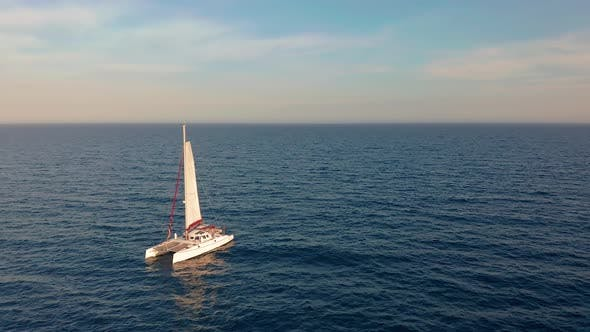 Catamaran Goes By Sea, Camera Move Closer and Fly Over Vessel, on the Sunset, Beautiful
