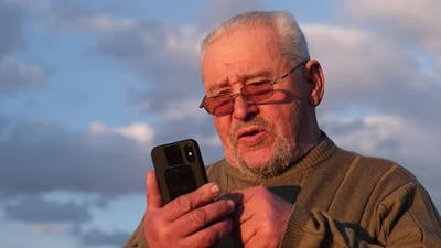 Smiling Old Man Chatting with Smartphone