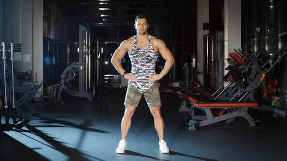 Thumbnail for Handsome Man Lifts Hands up Leans Torso Down and Stretches Back Gym