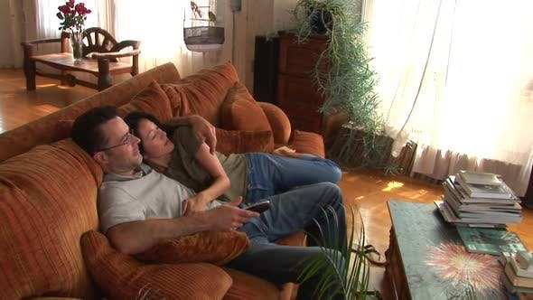 Thumbnail for Young couple on couch using remote to watch TV