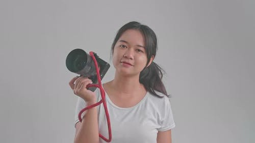 Young Asian Female Photographer Standing In Studio