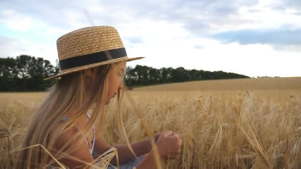 Thumbnail for Happy Small Child in Straw Hat Holding Cereal Spikelet in Hands While Sitting in the Wheat Field