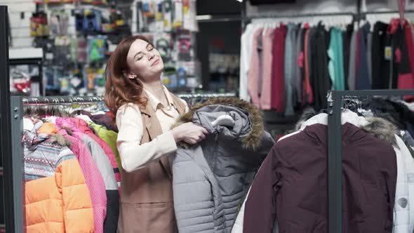 Thumbnail for Shopper, Charming Smiling Young Woman Loving Shopping Trying on Beautiful Jacket in Fashion Store
