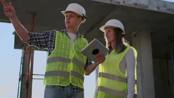 Thumbnail for Professional Engineers in Safety Vests and Helmets Working with Digital Tablet and Blueprints.