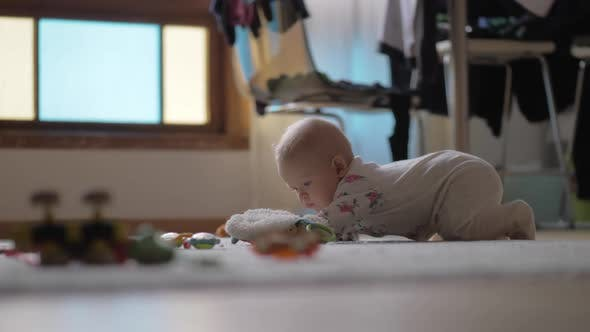 Baby Girl Crawling on the Floor with Toys