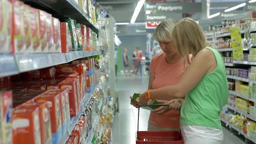 Women Checking Product Package in the Store