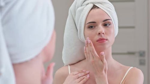 Young Female Stands in Front of the Mirror in Her Bathroom and Applies Cream on Her Face, Skin Care