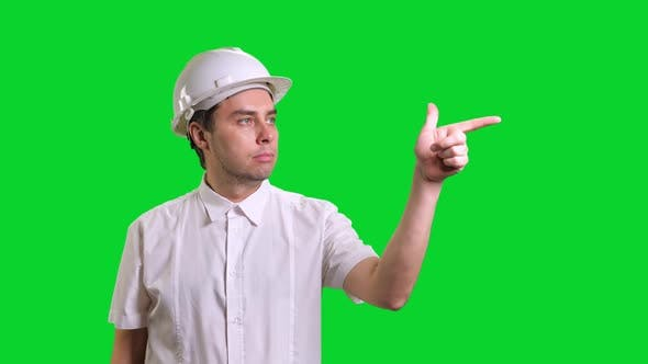 Young Male Engineer Standing and Pointing Aside on Green Screen Background