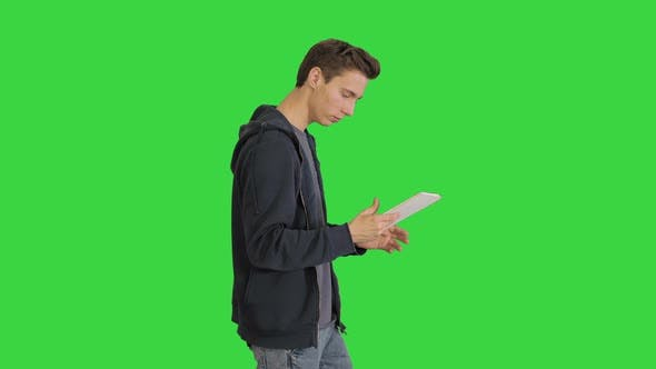 Thumbnail for çYoung Man Using Digital Tablet While Walking on a Green Screen, Chroma Key.