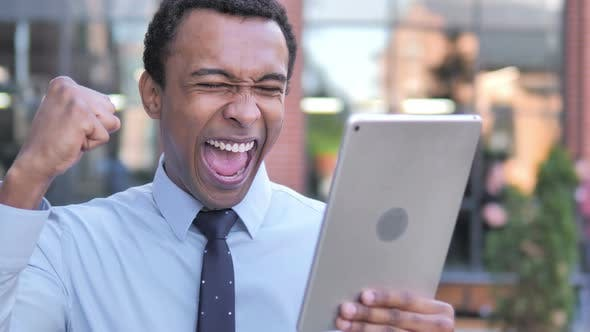 Thumbnail for African Businessman Cheering for Success on Tablet Outdoor
