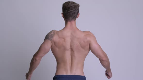 Cover Image for Rear View of Muscular Man Flexing Back Muscles and Biceps Shirtless