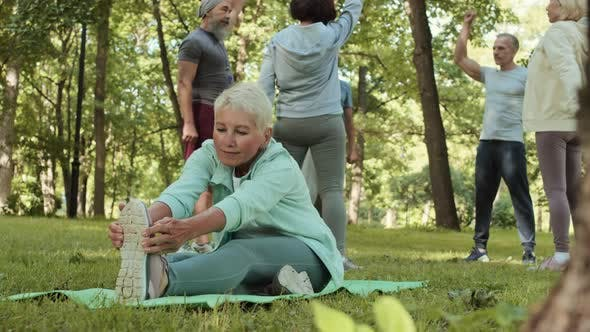 Aged Sportswoman Stretching in Park
