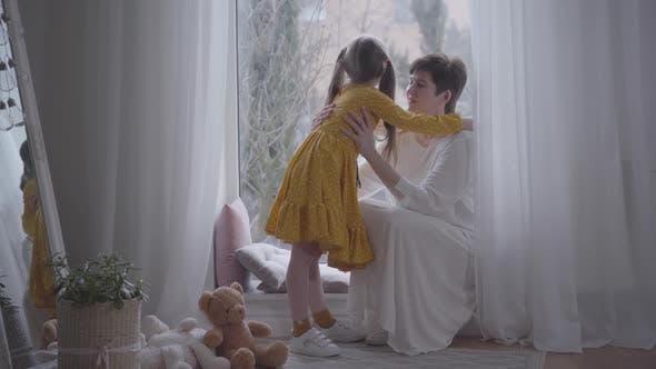 Élégante petite fille en robe jaune chuchotant secrets sur l'oreille de grand-mère en tenue blanche. Joyeux