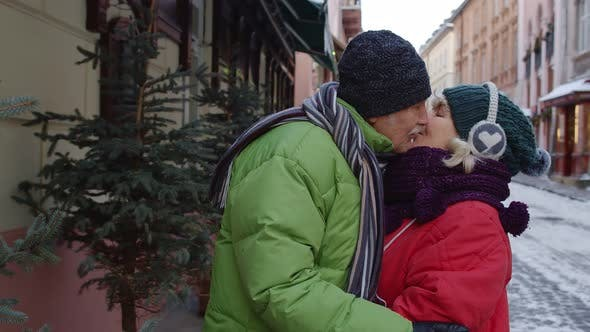 Thumbnail for Senior Elderly Couple Tourists Walking Hugging Making a Kiss in Winter City on Holidays Vacation