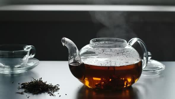 Thumbnail for Dampf aus einer Teekanne auf einem Tisch, In der Nähe ist Tee-Ernte und Glasbecher