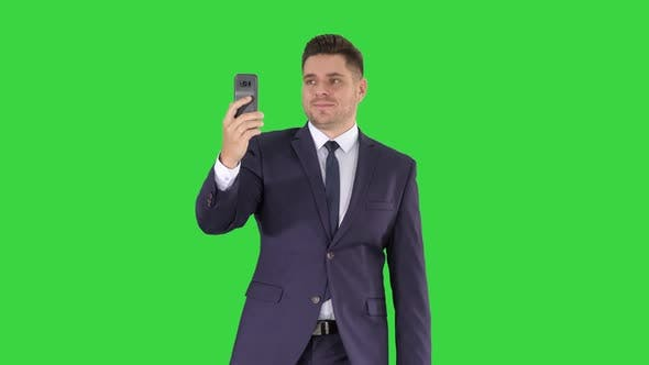 Thumbnail for Young Businessman Using Smartphone To Videocall To Business Partner While Walking on a Green Screen