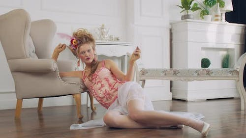 18Th Century Woman is Sitting on the Floor with a Feather in Hand Posing