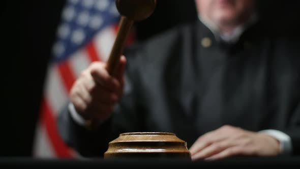Judge's Hand Banging A Gavel On Block Against American Flag In United States Court