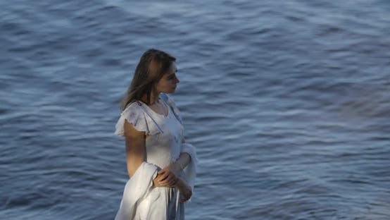 Thumbnail for Top View of a Beautiful Caucasian Woman in Light White Dress Standing on the Background of Sea Waves