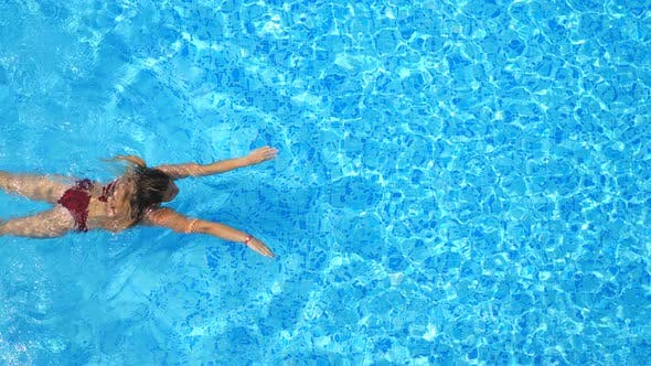 Thumbnail for Woman in Red Bikini Swimming Through Pool with Crystal Clear Water. Elegant Lady Relaxing