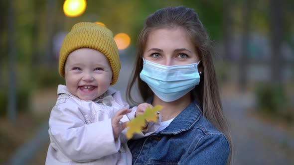 Thumbnail for Masked Mother Holds Hand Lovely Daughter on Street Walk During Second Wave Quarantine Coronavirus