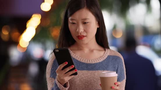 Cover Image for Close up of happy woman reading texts on smartphone in front of urban cafe
