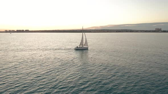 Cover Image for Aerial View. The Yacht Sails on the Sea at Sunset. Drone Flies Around the Yacht with Sails.